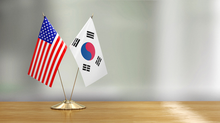 American and South Korean flag pair over defocused background