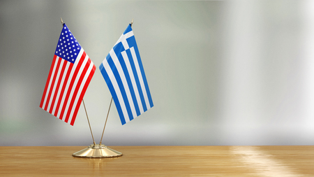 American and Greek flag pair over defocused background