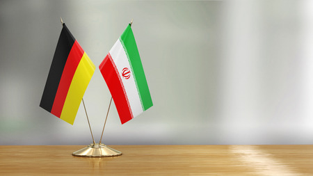 Iranian and German flag pair over defocused background Imagens - 124898148