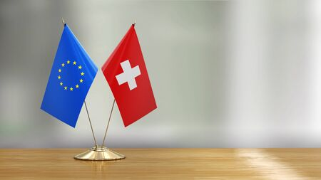 European Union and Swiss flag pair on a desk over defocused background