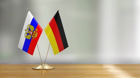 German and Russian flag pair on a desk over defocused background 免版税图像