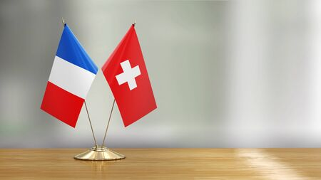 French and Swiss flag pair on a desk over defocused background