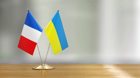 French and Ukrainian flag pair on a desk over defocused background