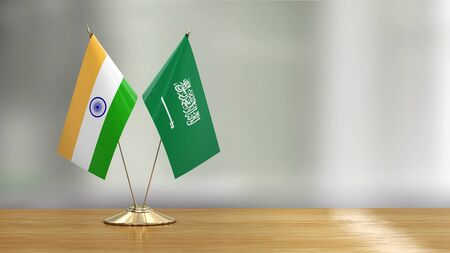 Saudi Arabia and Indian flag pair on a desk over defocused background