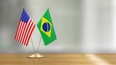 American and Brazilian flag pair on a desk over defocused background 免版税图像