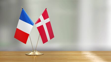 French and Danish flag pair on a desk over defocused background
