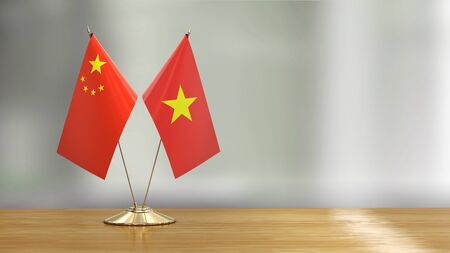 Chinese and Vietnamese flag pair on a desk over defocused background Stok Fotoğraf