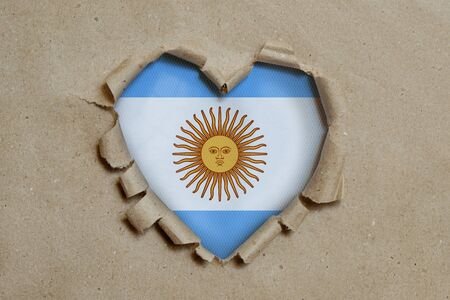 Heart shaped hole torn through paper, showing Argentina flag
