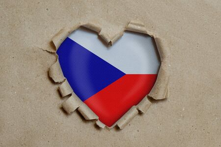 Heart shaped hole torn through paper, showing Czech flag Stockfoto