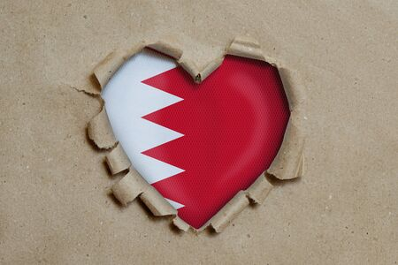 Heart shaped hole torn through paper, showing Bahrain flag