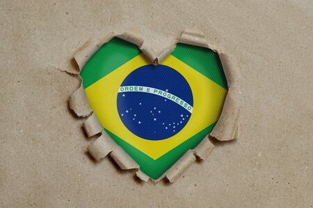 Heart shaped hole torn through paper, showing Brazilian flag Stockfoto