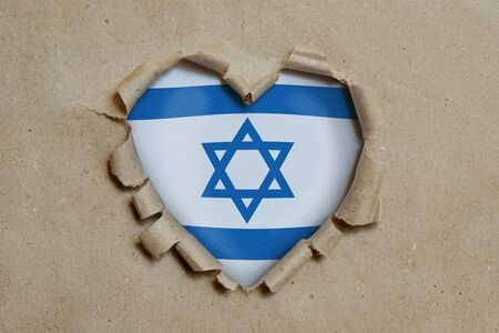 Heart shaped hole torn through paper, showing Israel flag