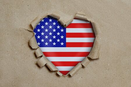 Heart shaped hole torn through paper, showing American flag Stock Photo