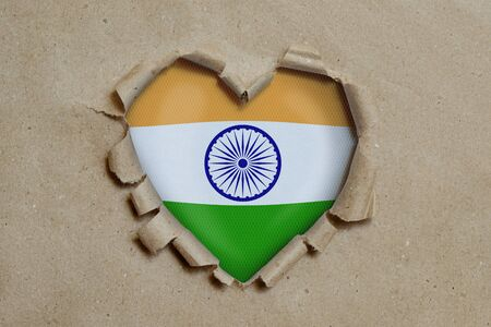 Heart shaped hole torn through paper, showing Indian flag Stockfoto