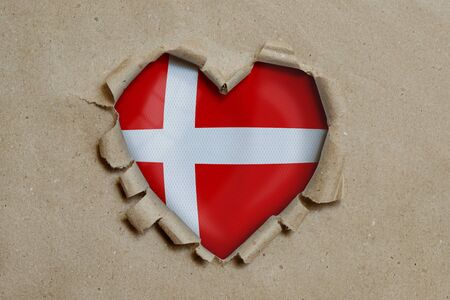 Heart shaped hole torn through paper, showing Danish flag