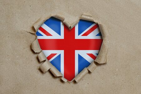 Heart shaped hole torn through paper, showing British flag