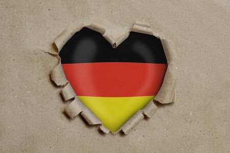 Heart shaped hole torn through paper, showing German flag Stock Photo