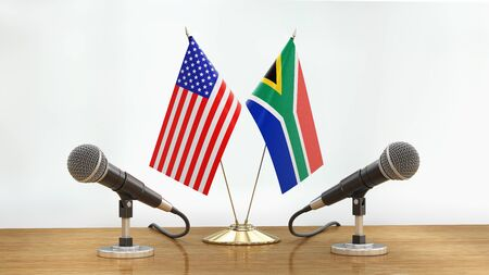 Microphones and flags pair on a desk over defocused background