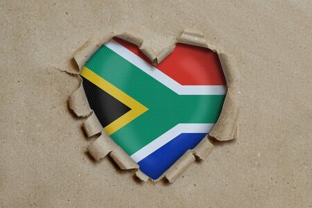 Heart shaped hole torn through paper, showing South African republic flag