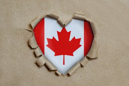 Heart shaped hole torn through paper, showing Canadian flag