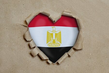 Heart shaped hole torn through paper, showing Egyptian flag Stock Photo