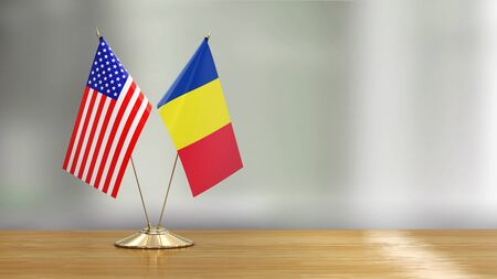 American and Romanian flag pair on a desk over defocused background 免版税图像