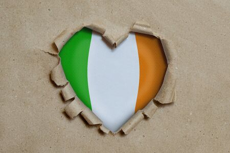 Heart shaped hole torn through paper, showing Irish flag