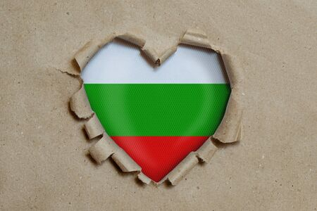 Heart shaped hole torn through paper, showing Bulgarian flag