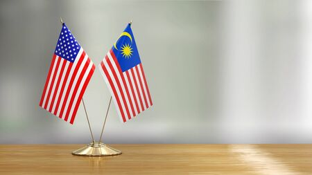 American and Malaysia flag pair on a desk over defocused background