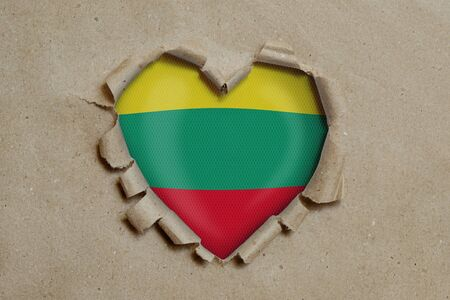 Heart shaped hole torn through paper, showing Lithuanian flag
