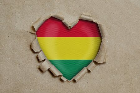 Heart shaped hole torn through paper, showing Bolivian flag