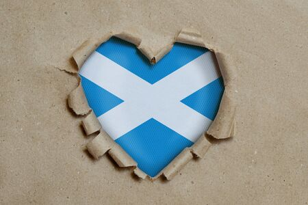 Heart shaped hole torn through paper, showing Scottish flag