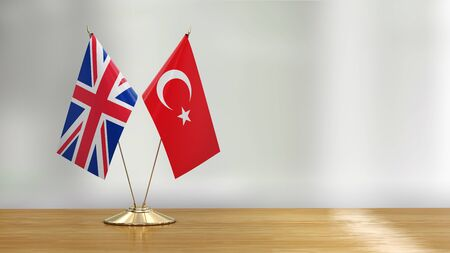 British and Turkish flag pair on a desk over defocused background