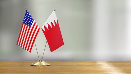 American and Bahrain flag pair on a desk over defocused background
