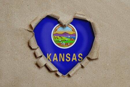 Heart shaped hole torn through paper, showing Kansas flag