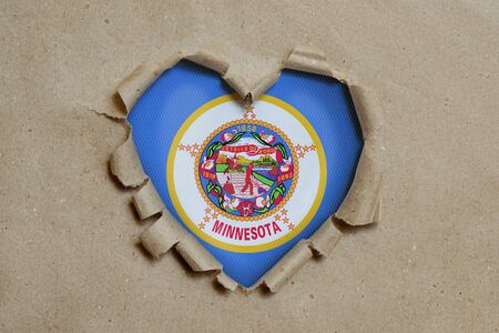Heart shaped hole torn through paper, showing Minnesota flag