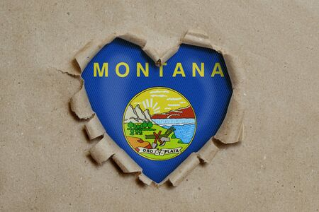Heart shaped hole torn through paper, showing Montana flag