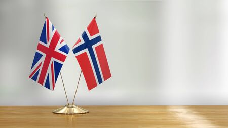 British and Norwegian flag pair on a desk over defocused background