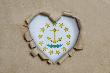 Heart shaped hole torn through paper, showing Rhode Island flag