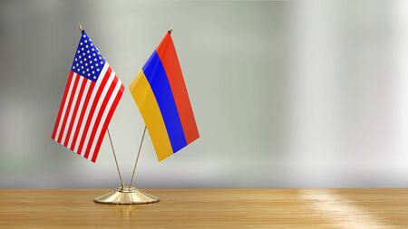 American and Armenian flag pair on a desk over defocused background 免版税图像
