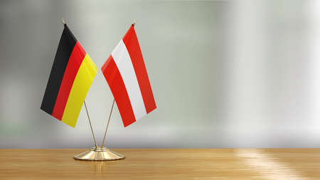 Austrian and German flag pair on a desk over defocused background
