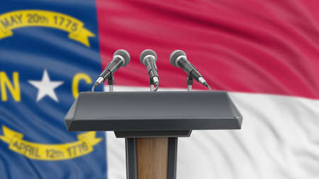 Podium lectern with microphones and North Carolina flag in background