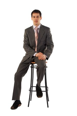 Young man sits on stool