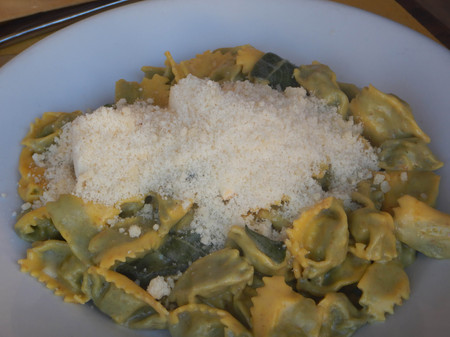 A dish of agnolotti with butter and sage in a dish with grated cheese ready to be eaten