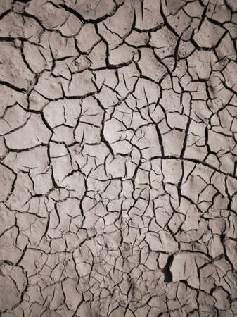 Texture of dry cracked earth. The desert background. The global shortage of water. Deep cracks in brown land as symbol of hot climate and drought. Imagens