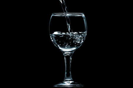 Pour water into glass on black background. Stock Photo