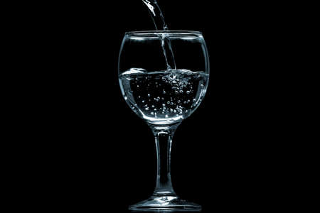 Pour water into glass on black background. Imagens