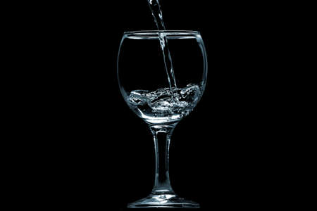 Pour water into glass on black background. Banco de Imagens
