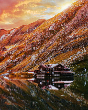 Bâlea Lake in the Făgăraș Mountains, Sibiu County. Reflection of the cottage in the water of the lake at sunset. Picture taken on August 30th, 2019.