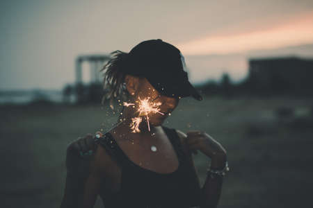 Portrait of young european girl holding sparkle stick under the patio outdoor. Happy smiling woman celebrating with fireworks